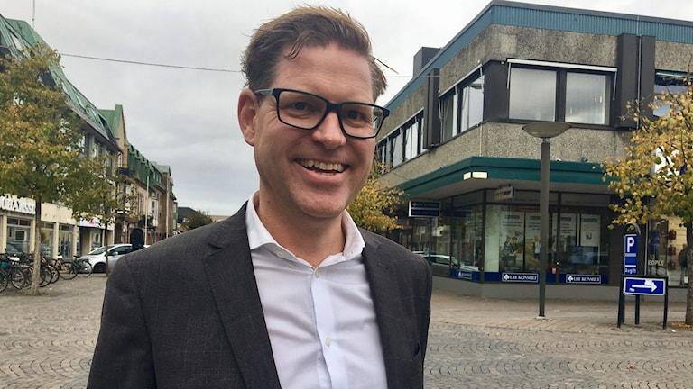 En leende man i glasögon står på en gata.