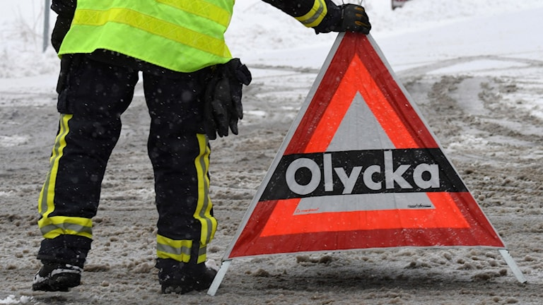 """Räddningspersonal ställer ut en skylt """"olycka"""" i på en snöig väg. Foto: Johan Nilsson/TT."""