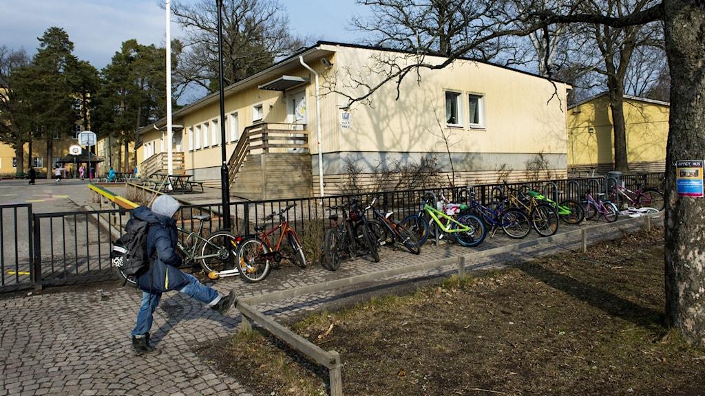 Gul skolpaviljong står på en skolgård.
