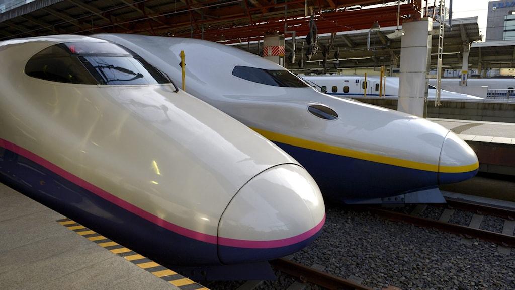 Två lok till japanska höghastighetståg står på en station.