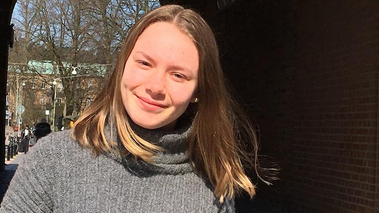 En ung kvinna står ute i solen och ler. Hon tittar in i kameran.