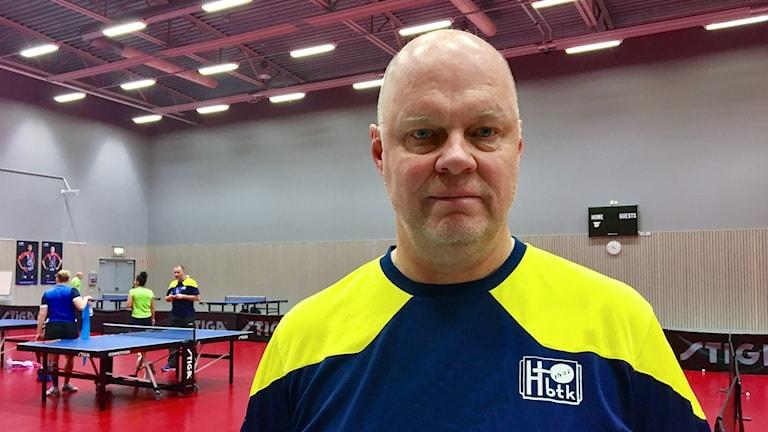 Ulf Tickan Carlsson står inne i en hall där det spelas pingis i bakgrunden.