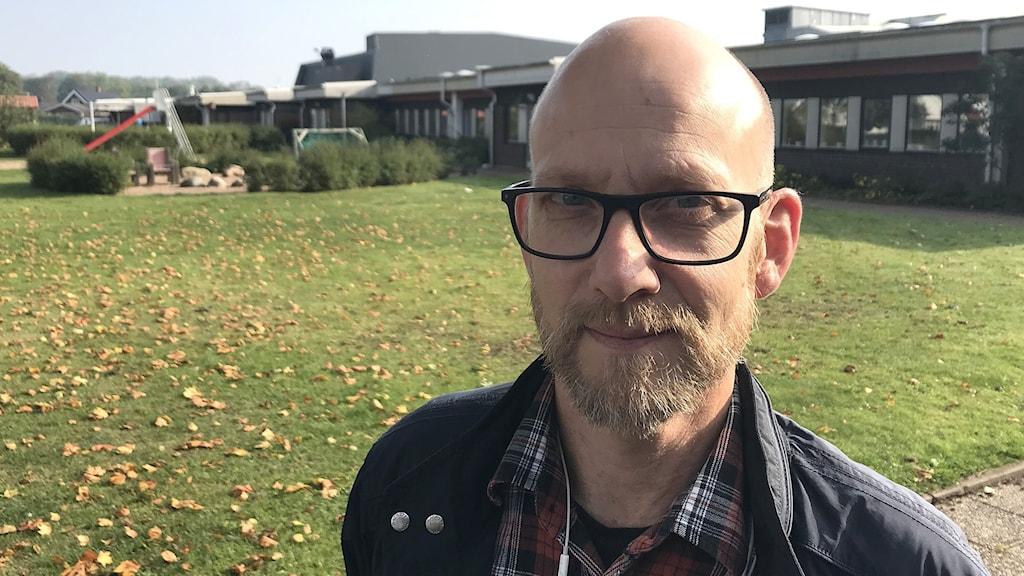 En man klädd i glasögon som står framför en gräsmatta och en skolbyggnad.