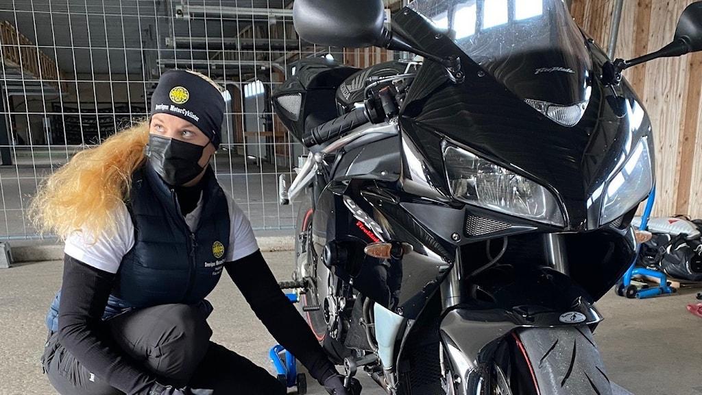 En kvinna visar hur man byter olja på en motorcykel.