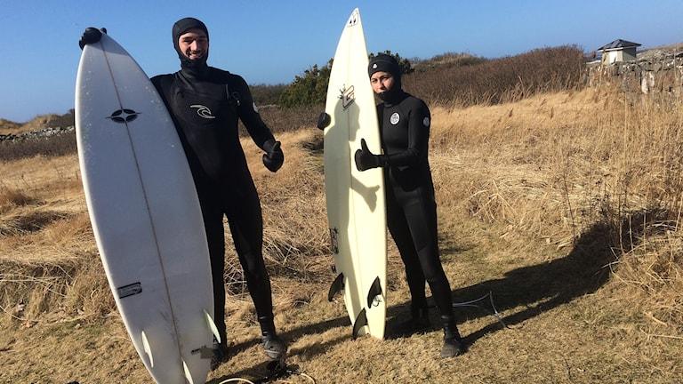 I sina svarta våtdräckter står Jonas och Nikola en bit från stranden i högs beiget torrt gräs. Brådorna står rätt up, lutandes mot marken. Kompisparet gör båda tummen upp. Solen lyser på dem.