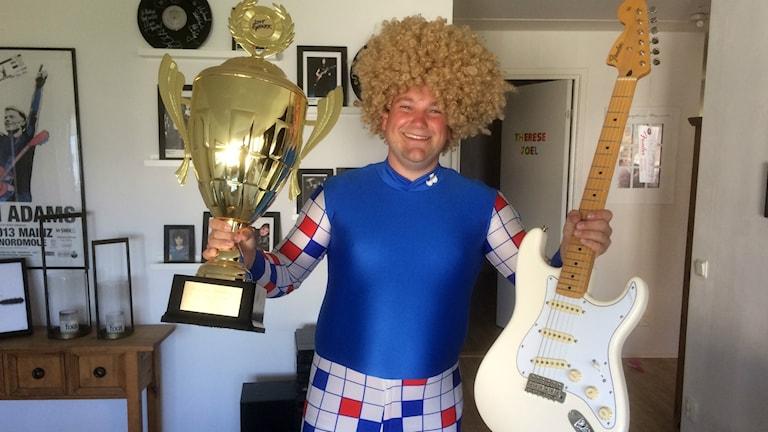 Mikael Goilarn Nyrén poserar med vinsten från SM i luftgitarr.