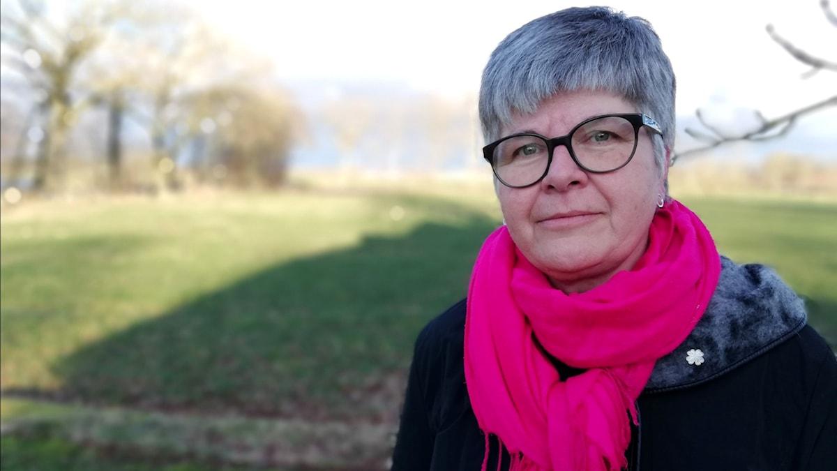 Kvinna med rosa halsduk.