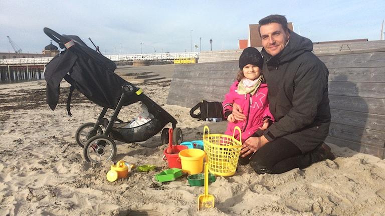 Tilo sitter i sanden med sin dotter på knäet.