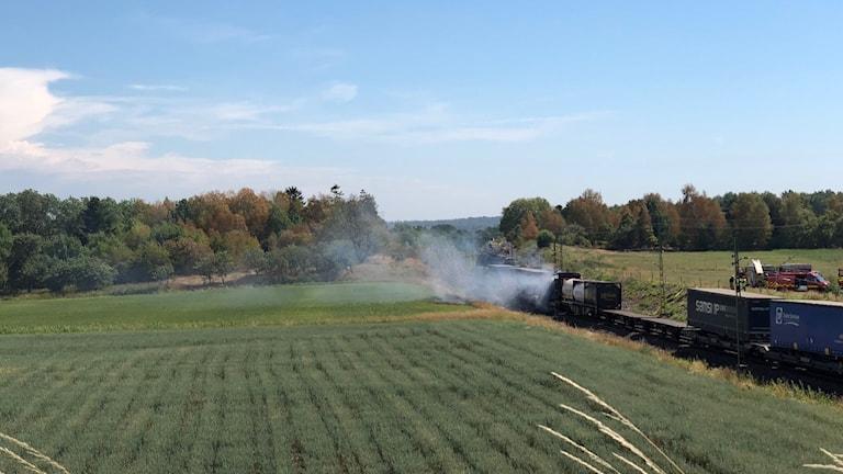 ett foto tagit på avstånd på tågvagnen som det ryker ur