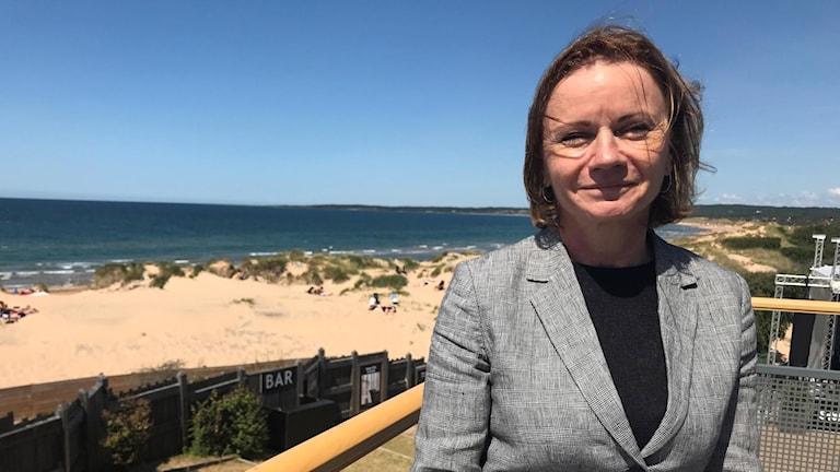 Kvinna står vid strand och ler.