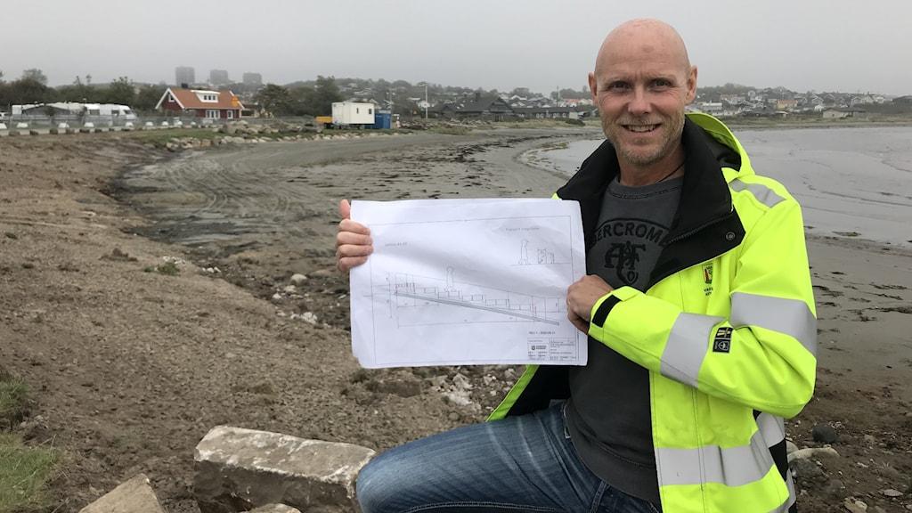 Anders Sivertsson står på byggarbetsplatsen på stranden och håller upp skisserna för soltrappan och strandpromenaden. Han har på sig en gul skyddsväst.
