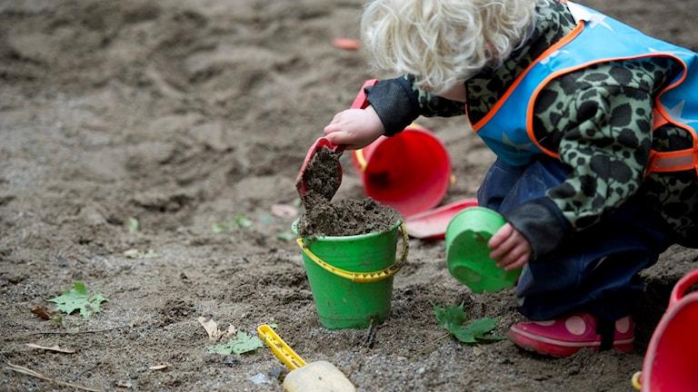 Barn som leker i sandlåda.