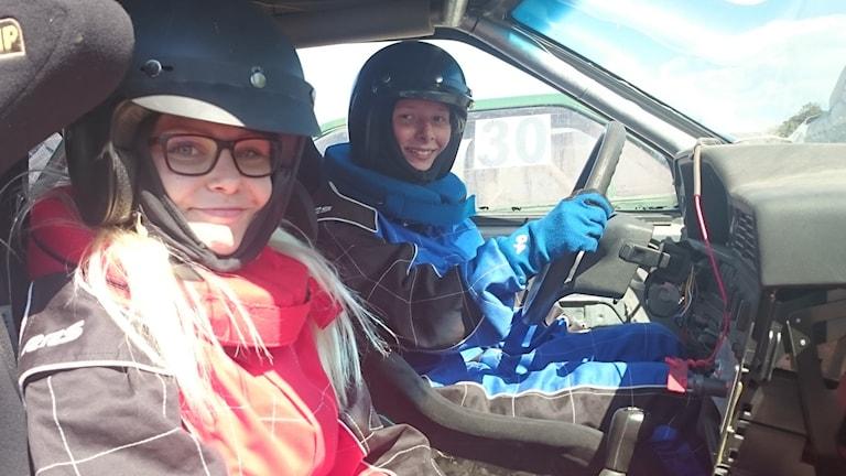 Porträtt av Linda Alminde och Jannike Aronsson i en folkracebil. De har hjälm och overall.