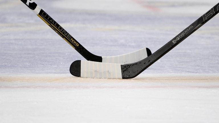 Två ishockeyklubbor.