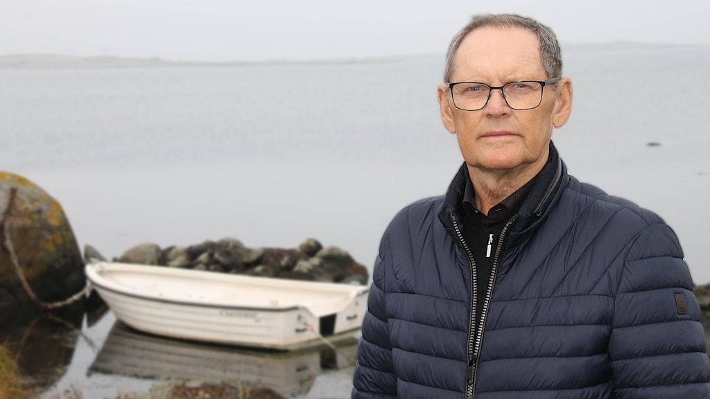 En man står i utomhusmiljö. I bakgrunden syns en båt utan båtmotor.