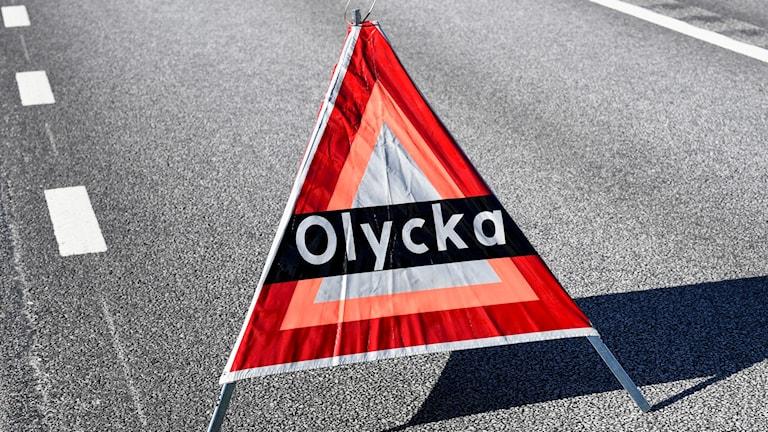 varningstriangel som står på vägen med texten olycka