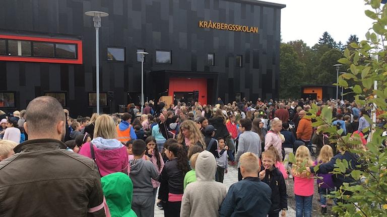 Bild av Kråkbergsskolan i bakgrunden och barn i förgrunden