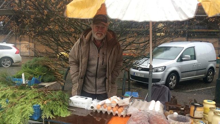 Janne Svensson, har skägg, keps och är iklädd en beige lång jacka. Han står under ett gult och vitt parasoll eftersom det regnar. På bordet framför honom finns vita och bruna ägg och burkar med honung.