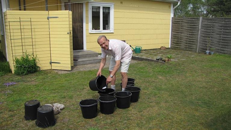 Stugägren Staffan Johansson ute i trädgården. Han håller på med hinkar.
