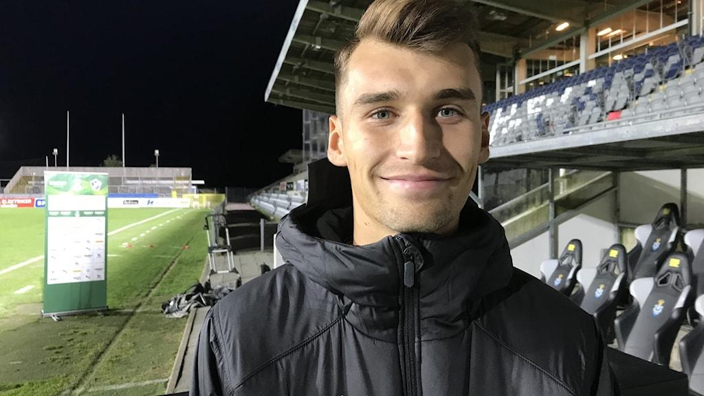 Rasmus Wiedesheim-Paul från Halmstad BK står vid fotbollsplanen.