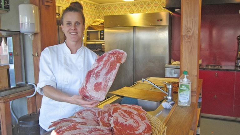 En kvinna iklädd vit tröja håller upp ett stycke kött.