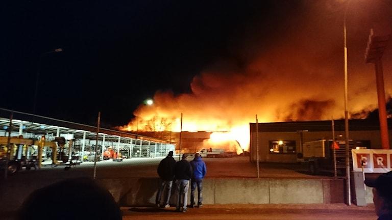Det brinner kraftigt i industrilokalerna. Utanför en mur står flera personer och tittar på lågorna. Det är natt.