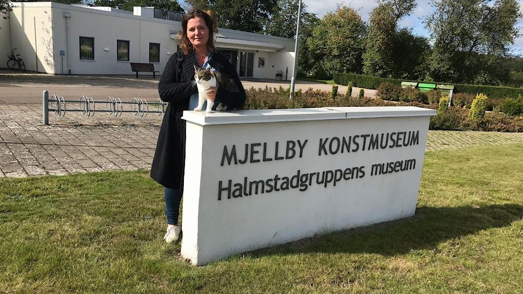 """Utsidan av Mjellby konstmuseum. På en stor stenskylt står texten """"Mjellby konstmuseum Halmstadgruppens museum"""". Vid den står en kvinna och på skylten står en katt. Kvinnan håller lätt om katten."""