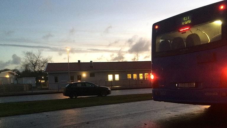 Till höger i bilden syns baksidan av en buss och till höger står en bil parkerad. I bakgrunden syns en del av skolan. Dagen börjar gry så himlen på bilden är ljus medan bilen, bussen och vägen som upptar halva bilden är mörk. Det lyser kraftigt från belysningen inne i skolan även från bussens röda lampor.