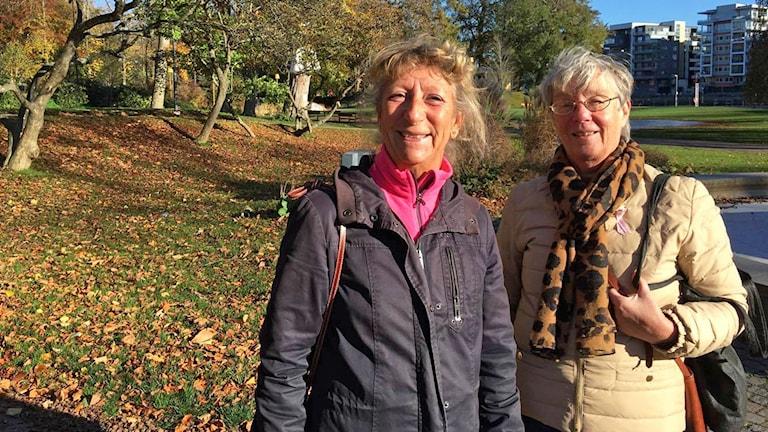 Två leende kvinnor står ute i ett höstklätt landskap i solen.