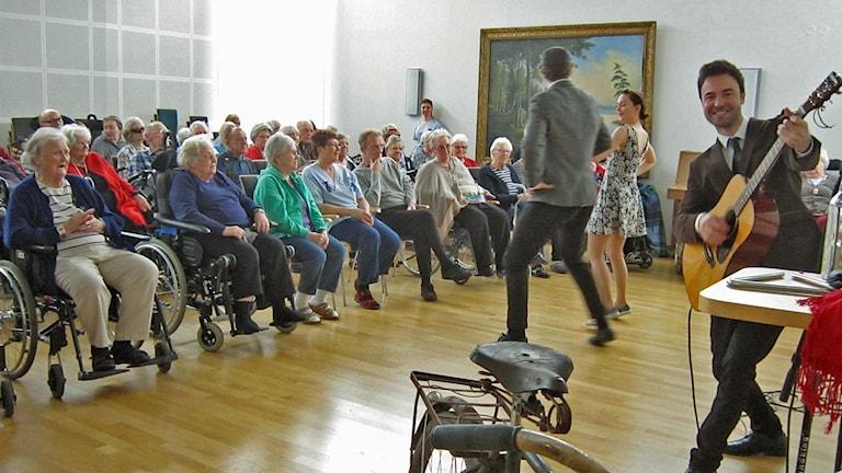 En man, vänd mot kameran, ler och spelar gitarr. En man och en kvinna dansar framför en publik av seniorer.