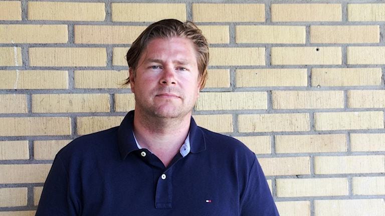 Porträtt av Benny Andrén mot gul tegelvägg.