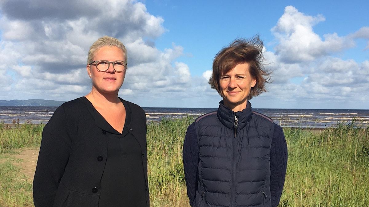Två kvinnor står på stranden. Några moln syns på himlen.