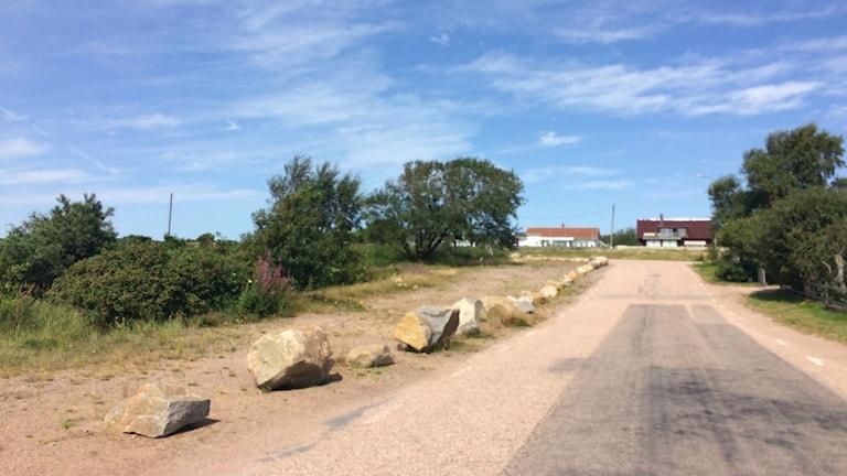 En väg med stenbumblingar som blockar en parkering.