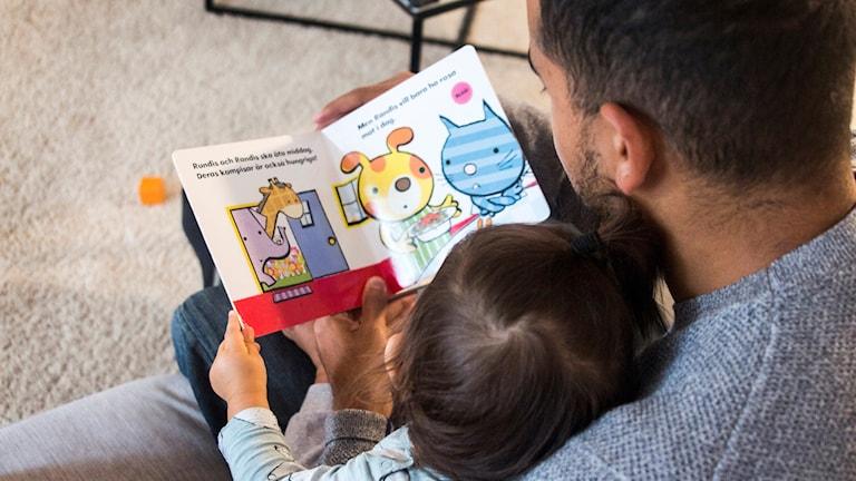Ett barn tillsammans med sin pappa läser en bok.