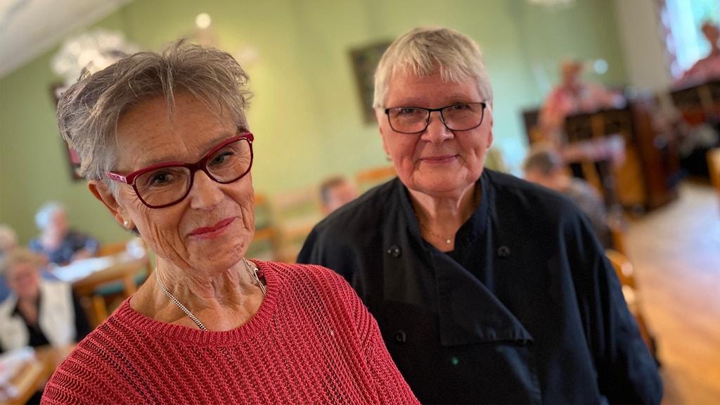 Två äldre kvinnor står i ett större rum. Det är flera personer i rummet. Kvinnorna tittar in i kameran och ler.