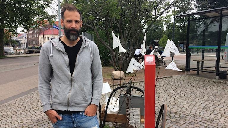 Projektledare Robert Hains framför det saboterade konstverket på Skansktorget.