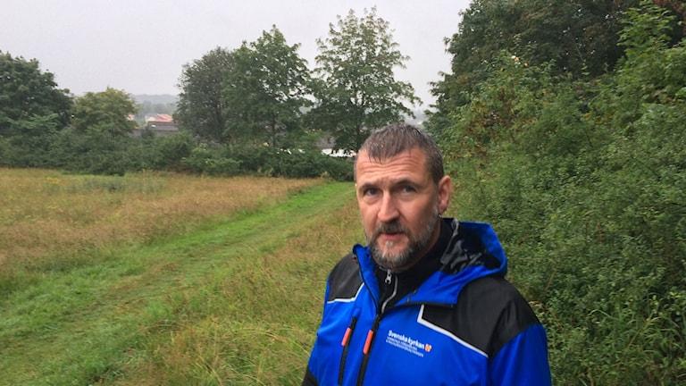 Fredrick Hallman står i regnet på en äng med en skogsdunge i bakgrunden.