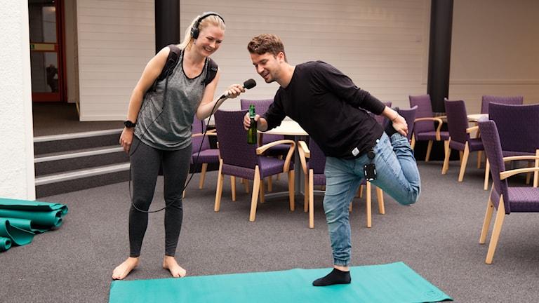 Reporter Daniel står på en yoga matta med en öl i handen. Yogainstruktören Emelie håller i mikrofonen.