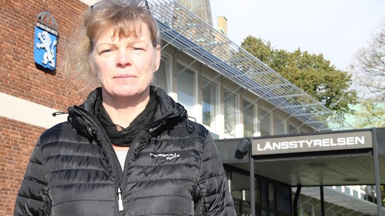 Viveca Eriksson ståendes i svart täckjacka framför ingången till Länsstyrelsen i Halmstad.