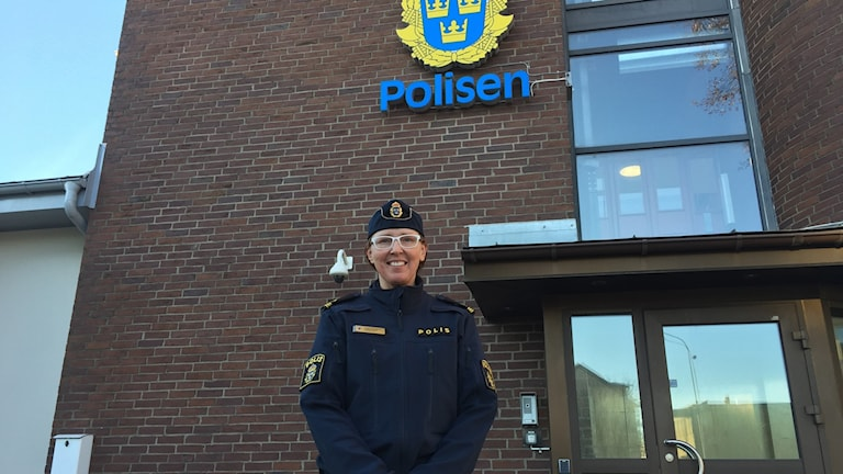 Poliskvinna framför polishus