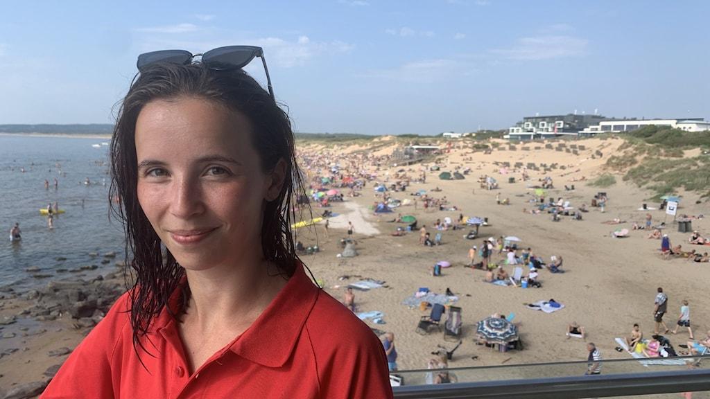 En kvinna sätter i framkant av bilden med solglasögon på huvudet och en röd tröja. I bakgrunden hav och en strand med massa folk.