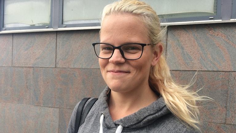 Nathalie Karlsson med blont hår, grå huvtröja och glasögon står framför en husvägg.