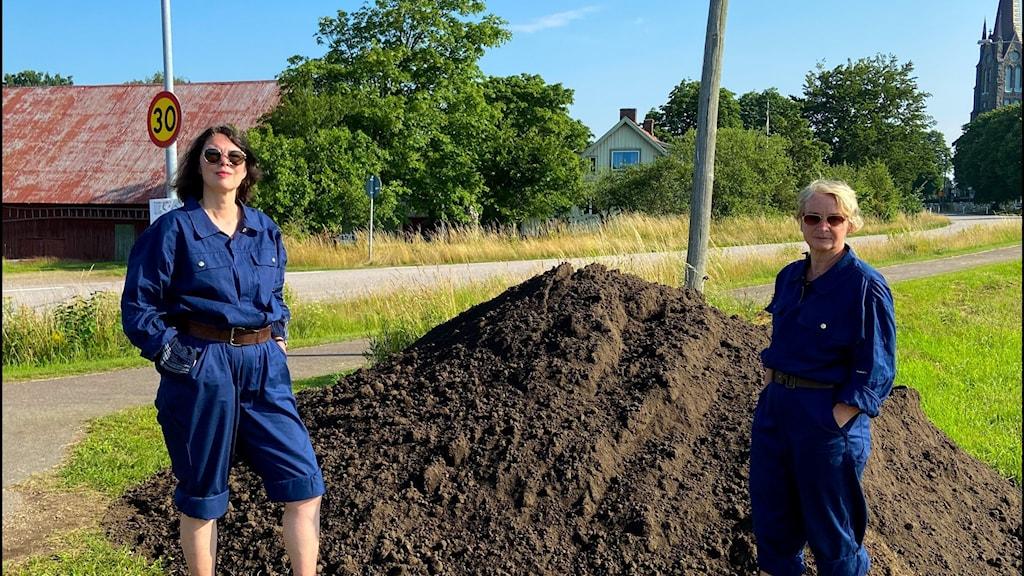 Konstnärerna Ulla Wikström och Ulla Mogren står framför en jordhög.