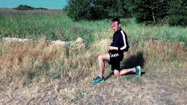 Philip Persson står och stretchar i gräset.