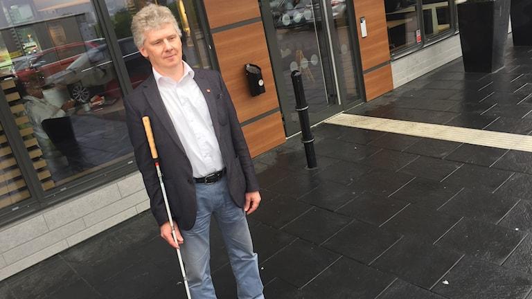 Niklas Mattsson står med sin vita käpp utanför en av McDonalds restauranger. Foto: Sveriges Radio