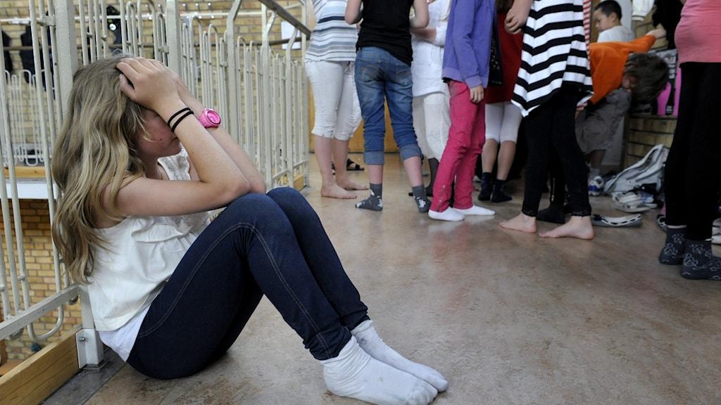 Bilden visar en flicka som sitter ner med händerna över ansiktet. Längre bort syns andra barn i en klunga.