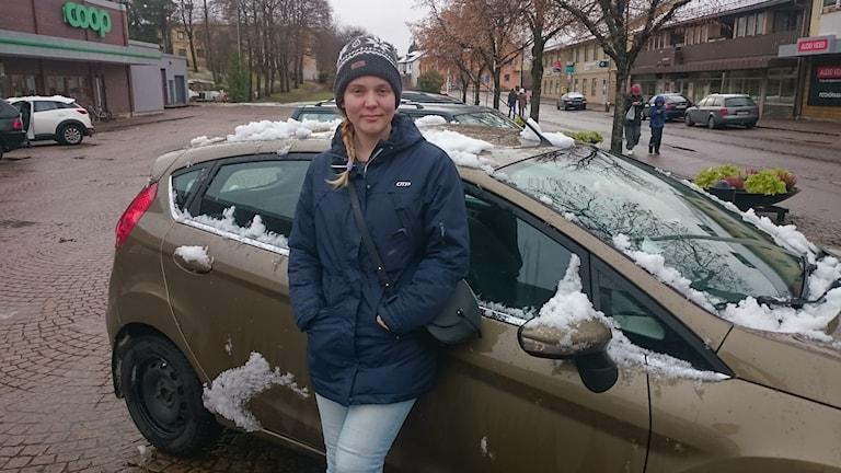 Tjej framför bil med snö på.