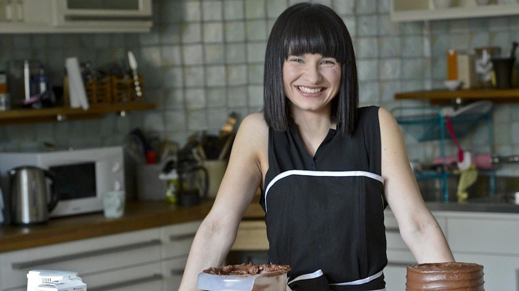 Bild på Linda Lomelino vid en köksbänk. På bänken står en tårta och ingredienser.