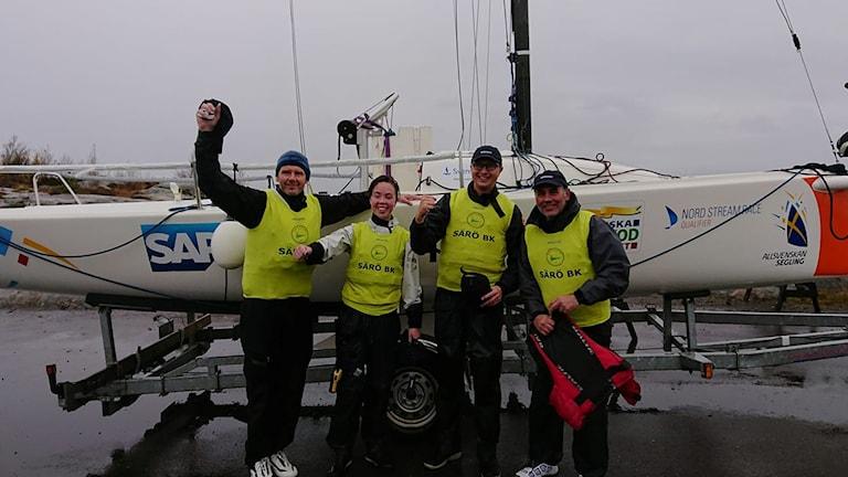 Fyra glada seglare iklädda gula västar jublar framför en segelbåt.