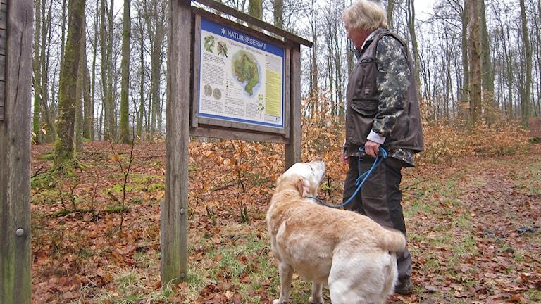 Ingrid Hammarlind och labradoren Bosse läser på vad som gäller i naturreservatet.